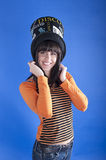 Cheerful girl in a hat on a blue background royalty free stock photo