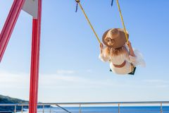 Cheerful girl in a hat and dress riding on a swing overlooking the sea. stock photography