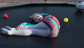 Cheerful girl having fun lying on trampoline Royalty Free Stock Photo