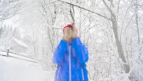 Woman is having fun - she is shaking the branches of a tree and snow is falling on her. Clear sunny frosty weather. Cheerful girl is having fun - she is shaking stock video