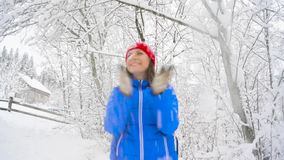 Woman is having fun - she is shaking the branches of a tree and snow is falling on her. Clear sunny frosty weather. Cheerful girl is having fun - she is shaking stock video footage