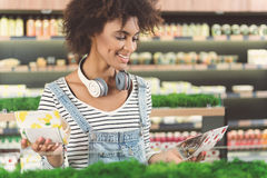 Cheerful girl with headphone on her neck buying natural sweets Royalty Free Stock Photo