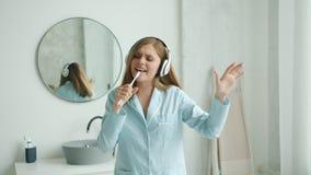 Cheerful girl in headphones brushing teeth singing dancing in bathroom at home. Cheerful girl in pajamas wearing wireless headphones is brushing teeth singing stock video footage
