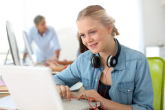 Cheerful girl with headphones using laptop Stock Photography