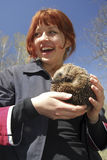 Cheerful girl with hedgehog. Red haired girl holding a little baby hedgehog royalty free stock photo