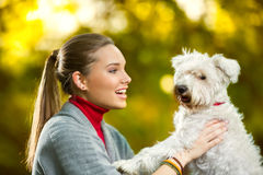 Cheerful girl with her cute puppy. Maltese in autumn park Royalty Free Stock Photo