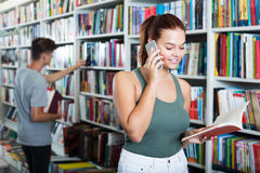 Cheerful  girl holding  book and talking on mobile phone Royalty Free Stock Photography