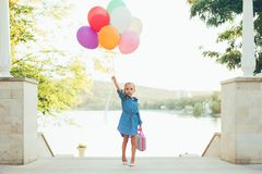 Cheerful girl holding colorful balloons and childish suitcase. Looking to camera, staying on the stairs in the park on lake and trees background, imagining she Royalty Free Stock Images