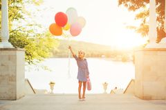 Cheerful girl holding colorful balloons and childish suitcase. Staying on the stairs in the city park on lake and trees background, imagining she travels Stock Photos