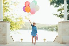 Cheerful girl holding colorful balloons and childish suitcase. Looking to sky, staying on the stairs in the park on lake and trees background, imagining she Royalty Free Stock Photos