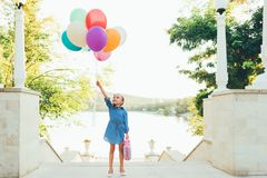 Cheerful girl holding colorful balloons and childish suitcase. Staying on the stairs in the city park on lake and trees background, imagining she travels Royalty Free Stock Photos
