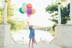 Cheerful girl holding colorful balloons and childish suitcase. Staying on the stairs in the city park on lake and trees background, imagining she travels Stock Photography