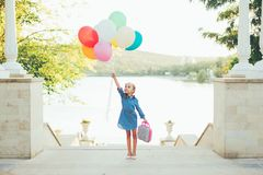 Cheerful girl holding colorful balloons and childish suitcase Stock Image