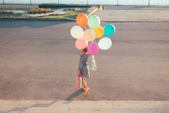 Cheerful girl holding colorful balloons and childish suitcase wa. Back view of girl holding colorful balloons and childish suitcase walking  in the city park on Royalty Free Stock Photo