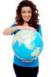 Cheerful girl holding globe safely with both hands Stock Photography
