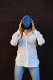 Cheerful girl holding hat hides her face Stock Image