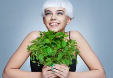 Cheerful girl holding organic mint bush on blue background. Royalty Free Stock Photo