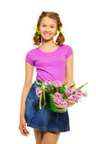 Cheerful girl holding pail with pink tulips. On the white background royalty free stock photo
