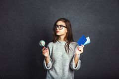 Girl with Passport and Plane Ticket. Cheerful girl holding passport, plane ticket and globe before grey background, indoor travel concept Stock Image