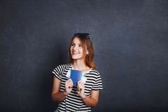 Girl with Passport and Plane Ticket. Cheerful girl holding passport, plane ticket and globe before grey background, indoor travel concept Stock Photography