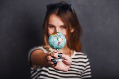 Girl with Passport and Plane Ticket. Cheerful girl holding passport, plane ticket and globe before grey background, indoor travel concept Royalty Free Stock Photos