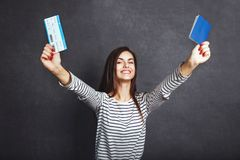 Girl with Passport and Plane Ticket. Cheerful girl holding passport, plane ticket before grey background, indoor travel concept Stock Photo