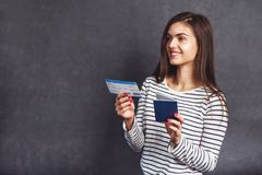 Girl with Passport and Plane Ticket. Cheerful girl holding passport, plane ticket before grey background, indoor travel concept Royalty Free Stock Photos
