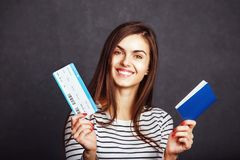 Girl with Passport and Plane Ticket. Cheerful girl holding passport, plane ticket before grey background, indoor travel concept Royalty Free Stock Photography