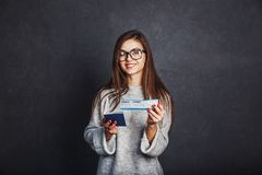 Girl with Passport and Plane Ticket. Cheerful girl holding passport, plane ticket before grey background, indoor travel concept Stock Photos