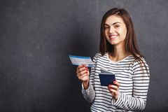 Girl with Passport and Plane Ticket. Cheerful girl holding passport, plane ticket before grey background, indoor travel concept Stock Photography
