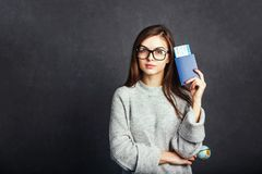Girl with Passport and Plane Ticket. Cheerful girl holding passport, plane ticket before grey background, indoor travel concept Royalty Free Stock Images