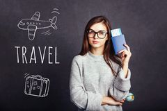 Girl with Passport and Plane Ticket. Cheerful girl holding passport, plane ticket before grey background, indoor travel concept Stock Image