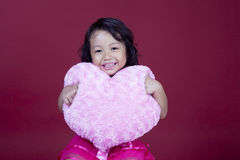 Cheerful girl holding pink heart Stock Photo