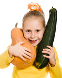 Cheerful girl holding a pumpkin and squash Stock Image