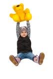 Cheerful girl holding a teddy bear on her head. Stock Photos