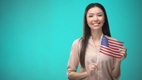 Cheerful girl holding USA flag, ready to learn foreign language, English school. Stock footage stock video footage