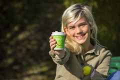 Cheerful girl. Holds a coffee Cup with the inscription `Enjoy Royalty Free Stock Images