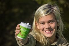 Cheerful girl. Holds a coffee Cup with the inscription `Enjoy Stock Photo