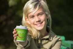 Cheerful girl. Holds a coffee Cup with the inscription `Enjoy Royalty Free Stock Image