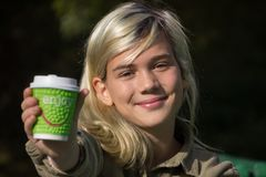 Cheerful girl. Holds a coffee Cup with the inscription `Enjoy Royalty Free Stock Photography