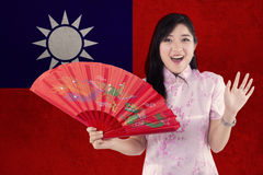 Cheerful girl holds a fan with Taiwan flag royalty free stock images