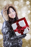 Cheerful girl holds gift while wearing winter clothes. Picture of happy teenage girl holding a gift box with red ribbon while wearing winter jacket Royalty Free Stock Image