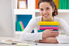 Cheerful girl hugging books Stock Photo