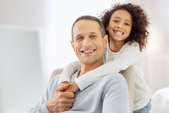 Cheerful girl hugging her daddy. Feeling inspired. Attractive joyful dark-haired father sitting in the arm-chair and smiling and his daughter standing behind him Royalty Free Stock Images