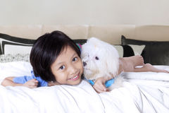 Cheerful girl hugs maltese dog on bed Royalty Free Stock Image