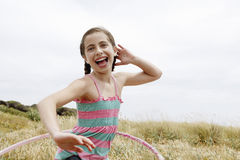 Cheerful Girl Hula Hooping In Field Stock Photos