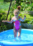 Cheerful girl in inflatable pool Stock Photography