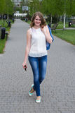 Cheerful girl in jeans comes in a park Stock Images