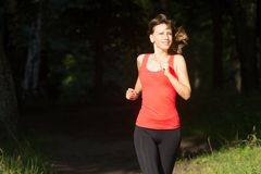Cheerful girl jogging at morning in summer park. Smiling young caucasian woman dressed in sportwear run out from shadow of the for. Est Royalty Free Stock Image