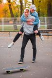 The girl jumped from behind on the guy in the skate park Stock Images